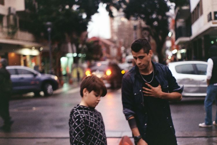 Father and son on street in city at sunset