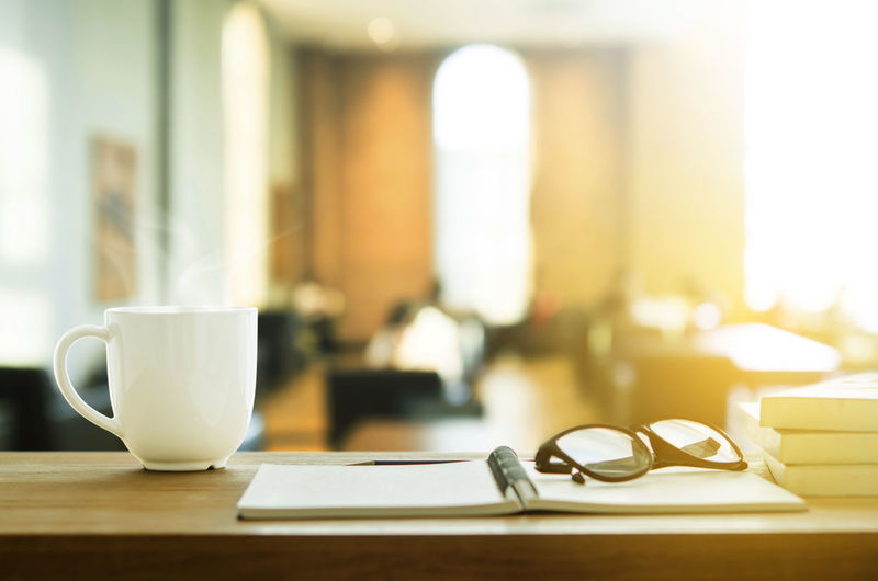 Close-up of coffee cup with diary and eyeglasses on table in cafe