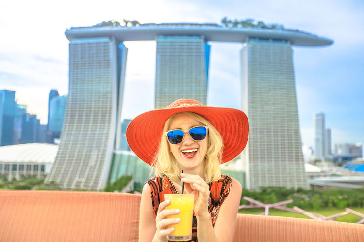 Happy tourist woman in travel holiday in Singapore, Southeast Asia. Lifestyle caucasian woman with red hat drinking at rooftop. Aerial view or cityscape skyline. Blue sky in a sunny day. Singapore Skyline Woman People Girl Aperitif Drink Orange Juice  Glass Aerial View Rooftop Architecture One Person Lifestyles Refreshment Real People Portrait Young Adult Fashion Leisure Activity Food And Drink Smiling Young Women Glasses Sunglasses Built Structure Building Exterior Day Emotion Outdoors Hair Cocktail Drinking