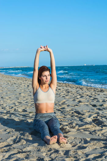 Young Woman Doing Yoga At Beach Against Clear Sky