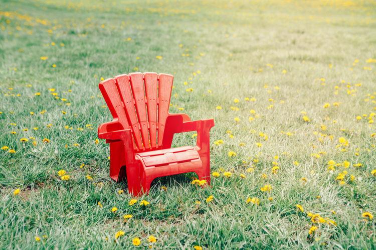 One red wooden plastic muskoka adirondack chair standing on green grass