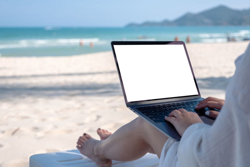 Mockup image of a woman holding and using laptop computer with blank desktop screen while laying down on beach chair on the beach Background Beach Black Blank Chair Communication Computer Connection Copy Copyspace Desktop Device Display Down Empty Female Girl Hand Holding Holiday Internet Laptop Laying Lifestyle Look Message Mock Mockup Nature Notebook Online  Over People person Relax Sand Screen Sea Shoulder Space
