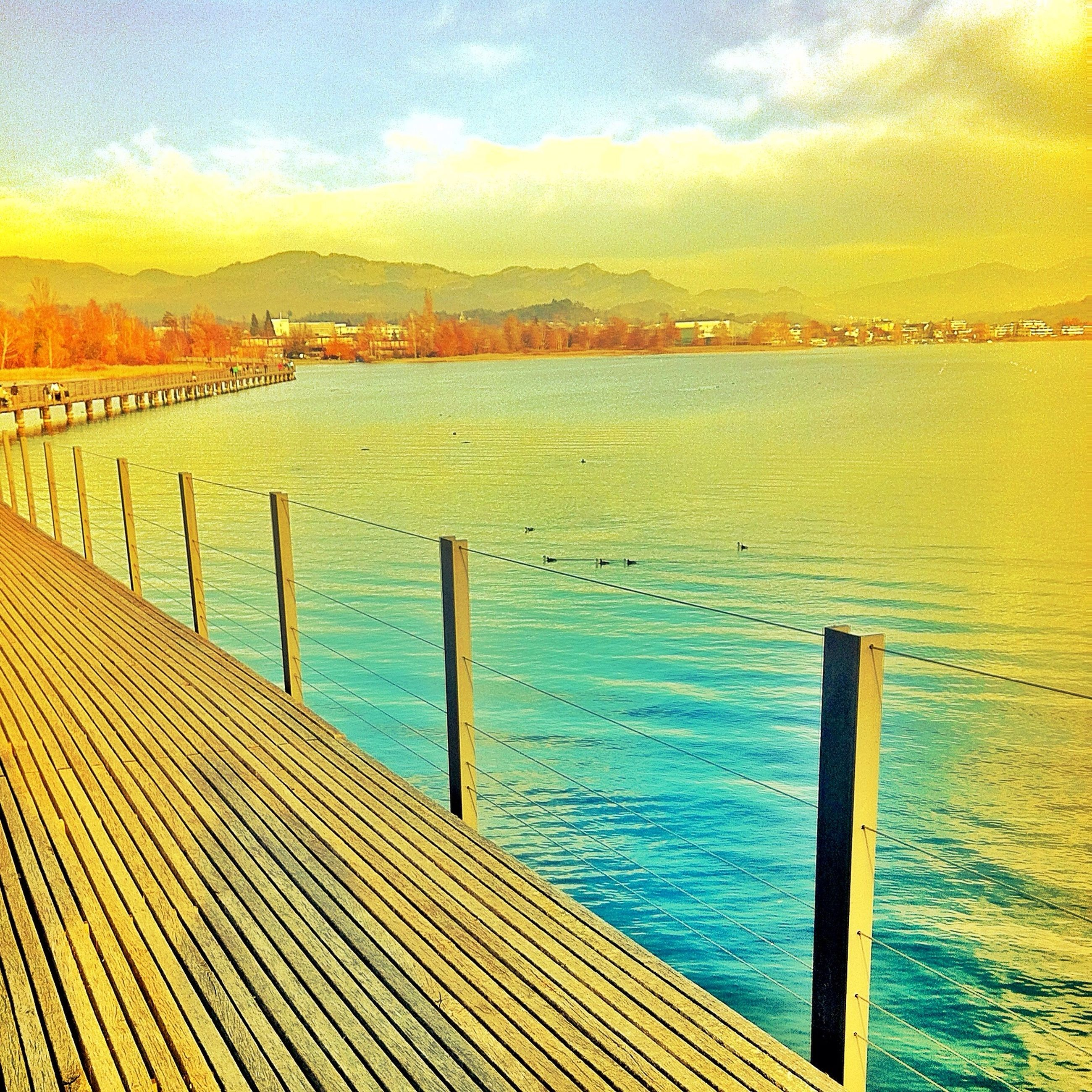 water, sea, tranquil scene, tranquility, scenics, pier, railing, sky, beauty in nature, nature, idyllic, wood - material, cloud - sky, rippled, jetty, cloud, fence, calm, mountain, ocean
