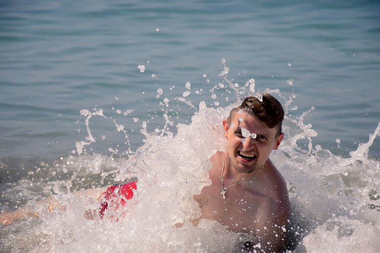 Portrait of cheerful young man diving in water at beach