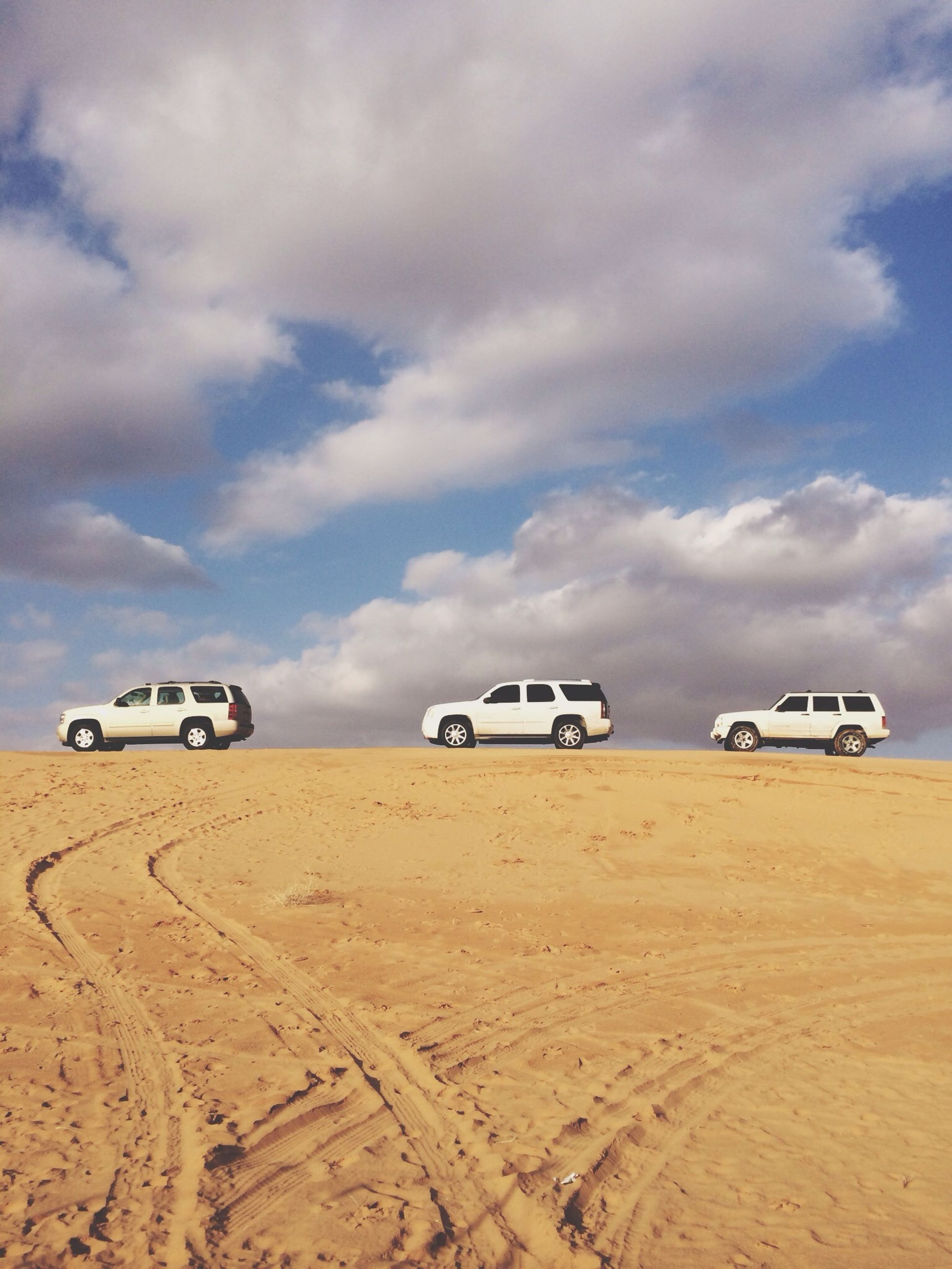 transportation, land vehicle, sand, mode of transport, car, sky, beach, desert, travel, cloud - sky, landscape, on the move, day, arid climate, outdoors, stationary, nature, sunlight, cloud, tranquility