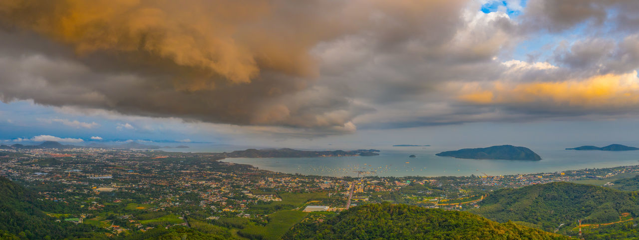A large cloud and thunderstorm covers Phuket island in sunset time Phuket Big Buddha Sunset, Storm, Religion, Church, Sect, Denomination, Belief, Ideology, Creed, Teaching, Doctrine, Moslem, Islam, Statue, Statue's, David, Florence Tourism, Cloud - Sky Sky Beauty In Nature Scenics - Nature Mountain Tranquility Sunset Tranquil Scene Environment Nature No People Dramatic Sky Outdoors Storm Non-urban Scene Landscape Aerial View Overcast Tree