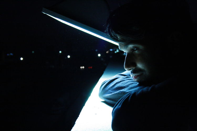 Portrait of young man looking away at night