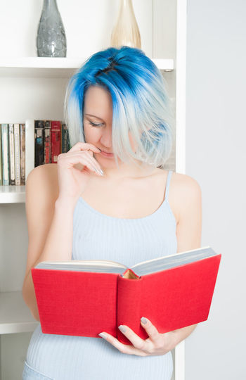 Woman with blue hair reading book