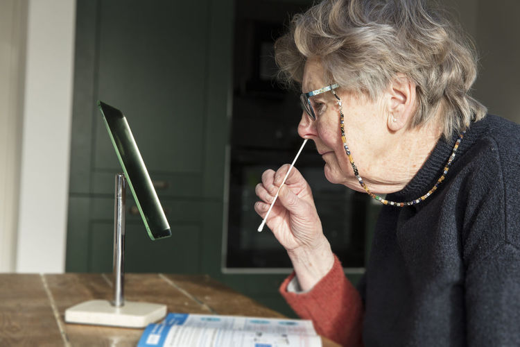 Woman putting cotton swab in nose