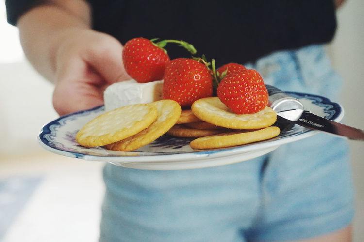 Midsection of woman holding biscuits with strawberries and cheese in plate