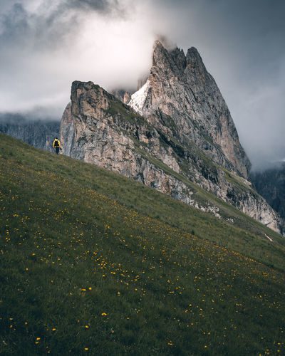 HIking man with a yellow raincoat against an impressive mountain with dramatic clouds Dolomites Dolomites, Italy Hiking Man Beauty In Nature Cliff Day Grass Green Color Hiking Trail Hikingadventures Landscape Mammal Mountain Mountain Range Mountains Nature Outdoors Peak Scenics Seceda Sky Slope Tranquil Scene Tranquility