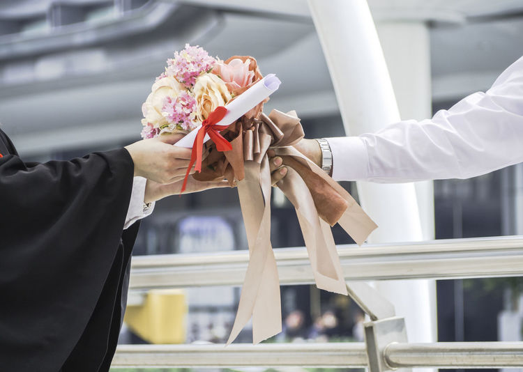 Cropped hands of people holding diploma and bouquet at college campus