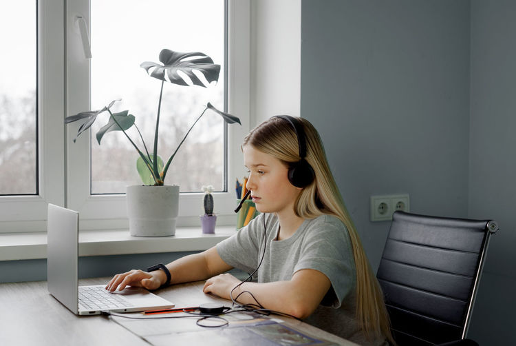 Teenage girl in headphones typing something on her laptop while having online lesson at home