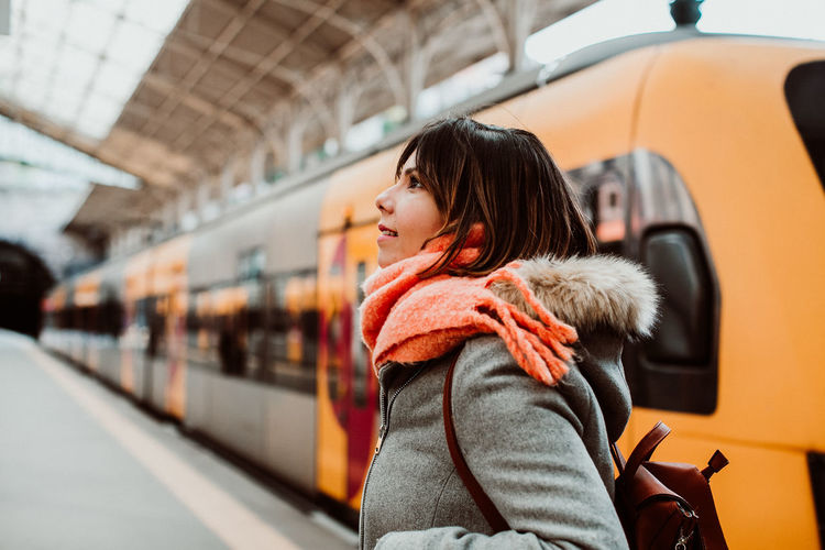 Woman looking at train in city during winter