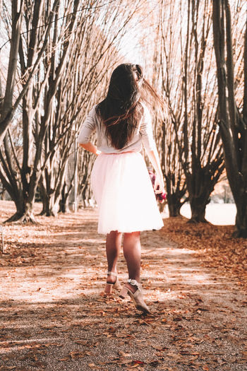 Full length rear view of woman walking on bare tree