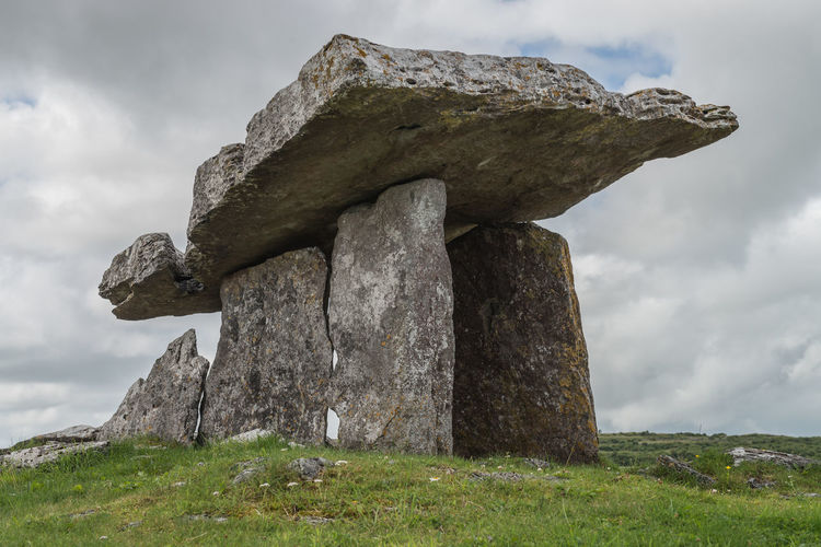 Stone structure on field against sky