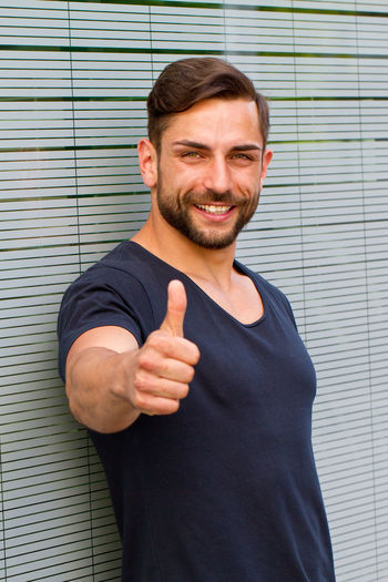 Young man with thumb up Business Man Positive Young Beard Business Finance And Industry Cheerful Finance Fitness Future Handsome Happiness Health Healthy Insurance Looking At Camera Men People Portrait Smiling Success Successful Thumb Up Thump Up