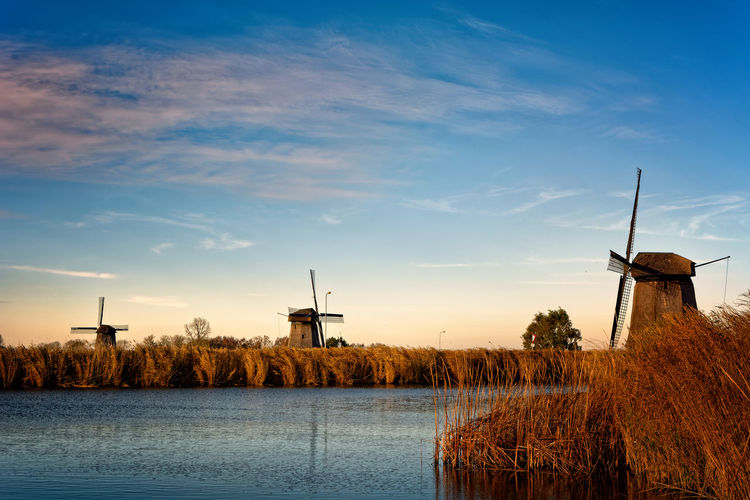 Traditional windmill against sky at sunset