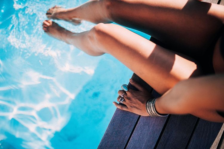 Low section of woman legs at swimming pool