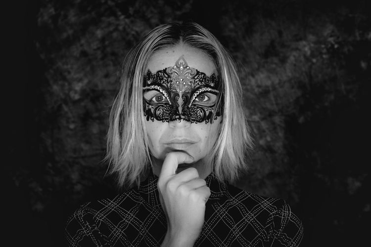 Close-Up Portrait Of Young Woman Wearing Masquerade Mask Against Wall