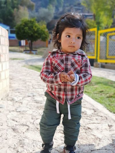 Full length of cute baby boy standing on footpath