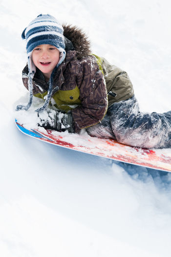 Cute boy tobogganing on snow covered land