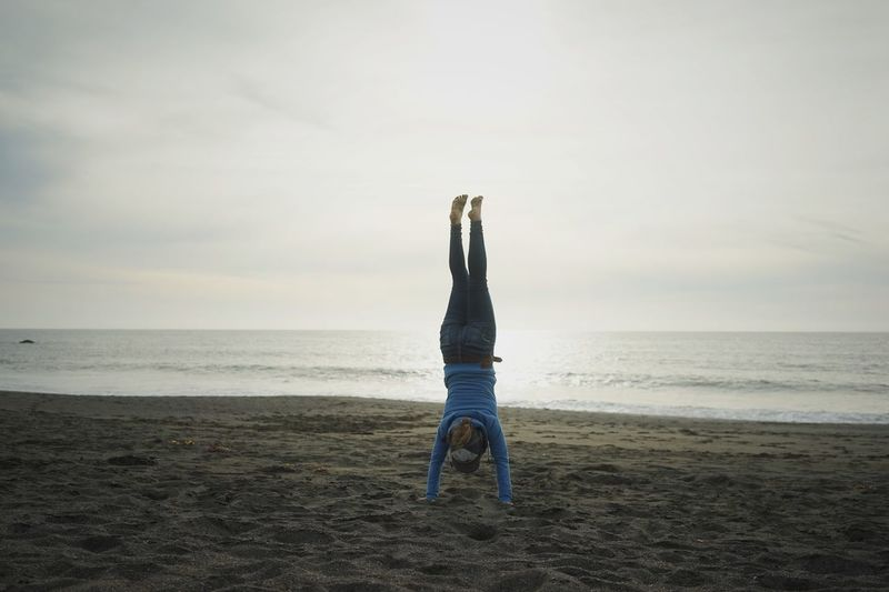 Woman Performing Headstand On Beach Against Cloudy Sky