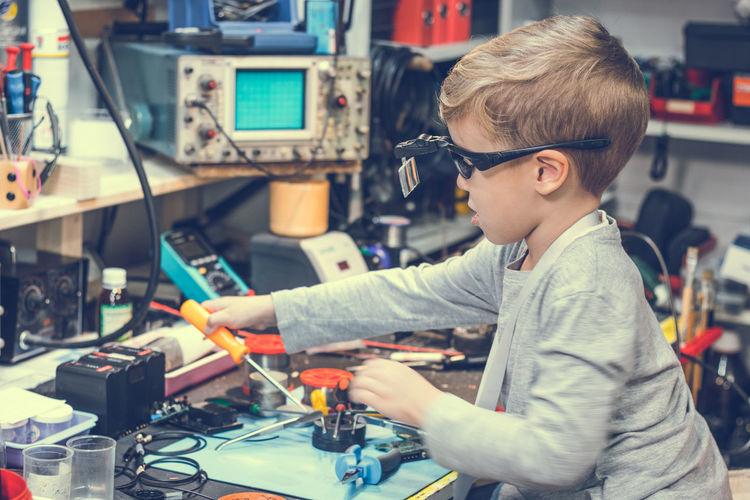 Side view of boy repairing equipment on table in workshop