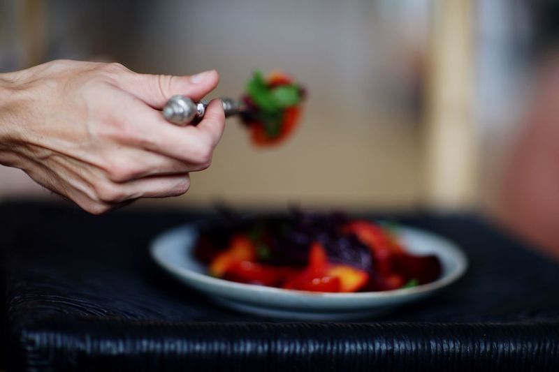 Cropped Hand Holding Food In Spoon