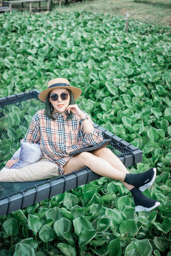 Chilling Fashion Balenciaga Beautiful Woman Burberry Casual Clothing Day Fashion Fashion Photography Full Length Glasses Green Color Growth Hat Leisure Activity Lifestyles Nature One Person Outdoors Plant Real People Relaxation Sitting Sunglasses Women