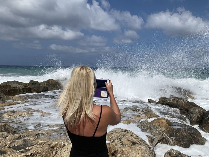Rear view of woman photographing sea with mobile phone at beach against sky