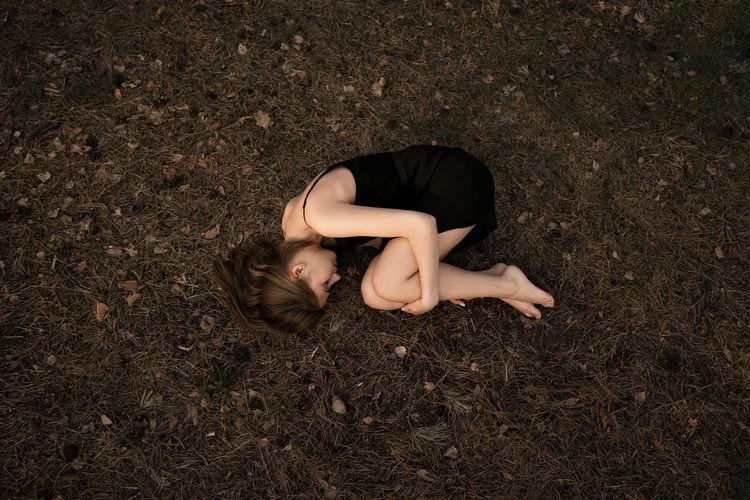 High angle view of woman lying on land