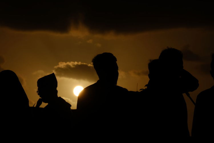 Silhouette people against sky during sunset