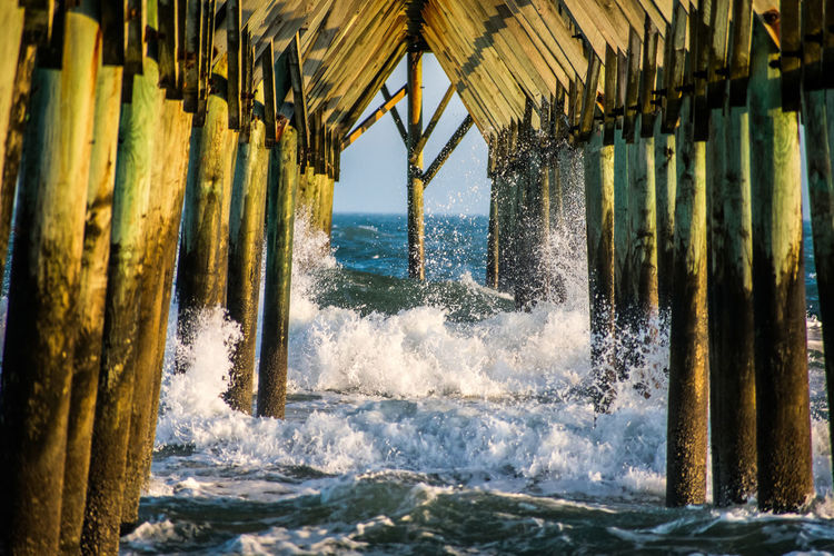 Under the Pier EyeEmNewHere Aquatic Sport Architecture Beach Beauty In Nature Built Structure Day Horizon Horizon Over Water Motion Nature No People Outdoors Pier Power In Nature Sea Splashing Water Wave Wood - Material
