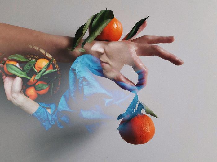 Midsection of man holding orange fruit against white background