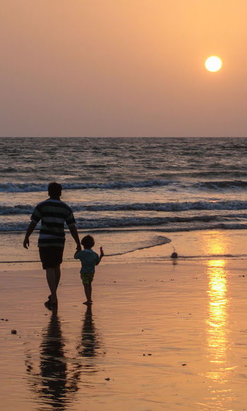 Father and son (and sun) Beach Beauty In Nature Horizon Horizon Over Water Land Leisure Activity Men Orange Color Real People Reflection Scenics - Nature Sea Silhouette Sky Sun Sunset Togetherness Two People Walking Water