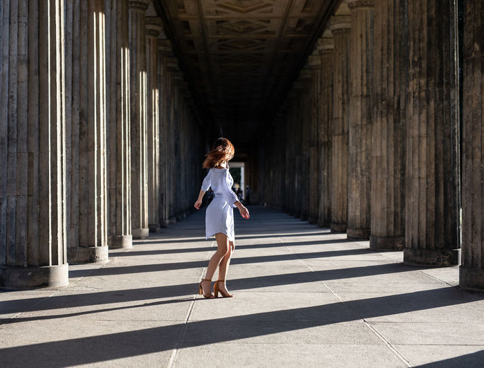 Side view of woman standing at colonnade
