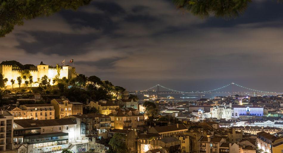 Illuminated cityscape by 25 de abril bridge against sky at night