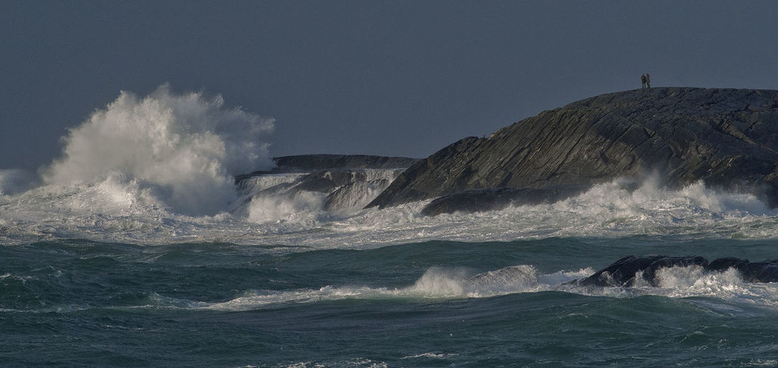 Sea waves splashing against clear sky