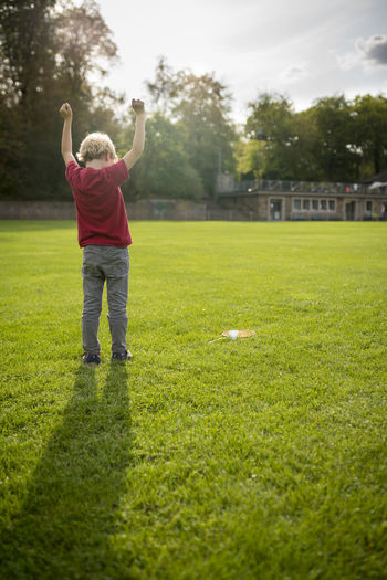 Rear View Of Boy With Arms Raised Standing On Grassy Field