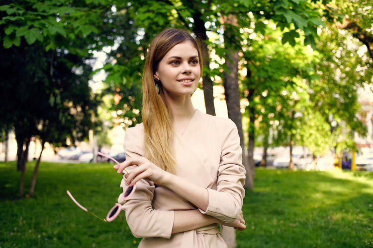 Portrait of smiling young woman standing on mobile phone