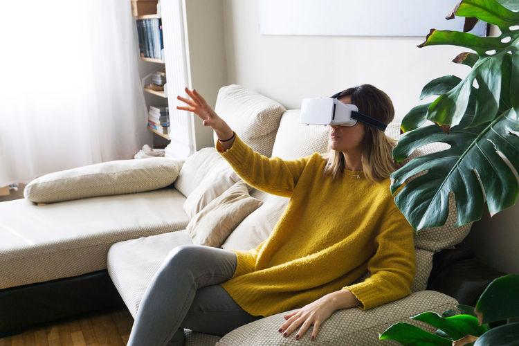 Young woman using virtual reality simulator on sofa at home