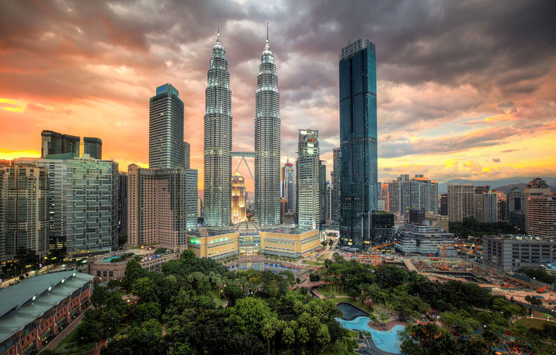 the twin petronas towers lit up under a kuala lumpur sunset ASIA KLCC Twin Towers Kuala Lumpur Light Architecture Building Building Exterior Built Structure City Cityscape Cloud - Sky Financial District  Illuminated Landmark Malaysia Modern Nature No People Office Office Building Exterior Outdoors Petronas Tower Residential District Sky Skyscraper Sunset Tall - High Tower Tree Twin Tower Urban Skyline