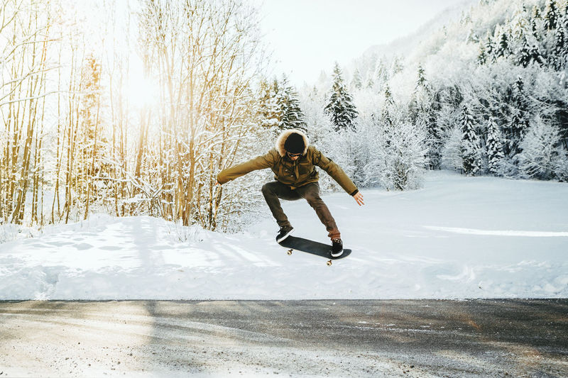 Skateboarder doing ollie trick on a frozen road Cold Temperature Day Extreme Sports Full Length Human Arm Jumping Leisure Activity Lifestyles Men Mid-air Motion Nature One Person Outdoors Plant Real People Skate Trick Skateboard Skill  Snow Sport Tree Warm Clothing Winter Winter Sport