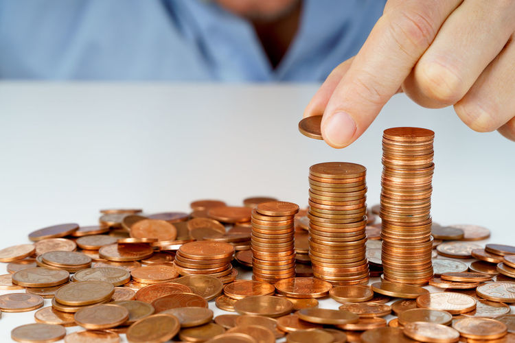 Cropped Hand Stacking Coins On White Table