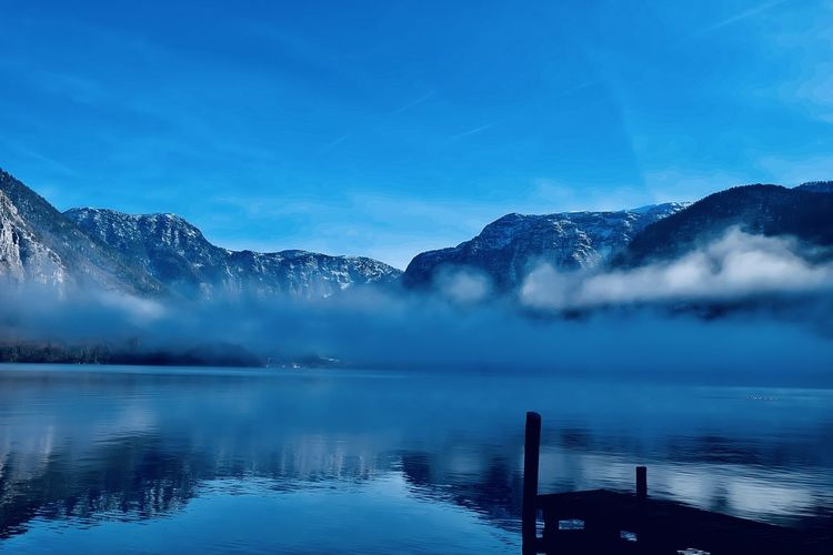 Scenic view of lake by mountains against blue sky