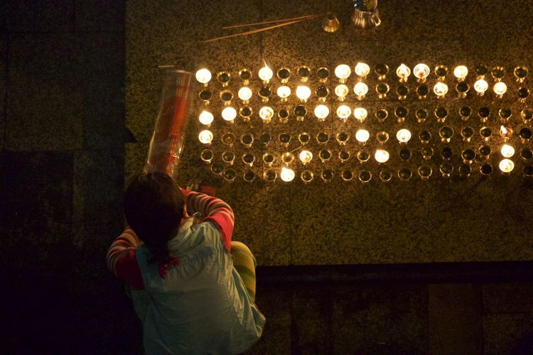 Rear View Of Woman Lighting Lamps At Temple