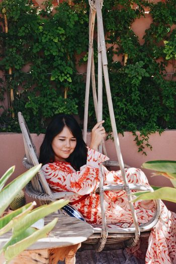 Portrait of smiling woman sitting on swing