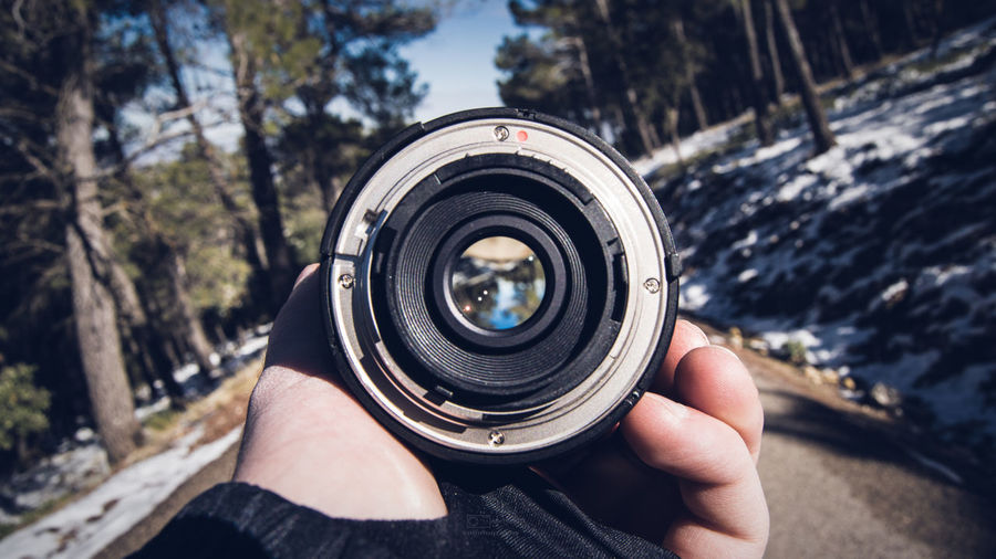 Cropped image of hand holding lens
