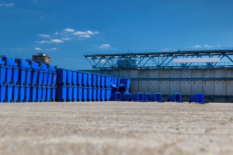 Blue garbage bins on field against sky